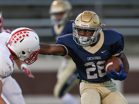 Cathedral running back Chon'Dre Cissell (26) stiff arms Center Grove's Lucas Roehling (21) during first quarter action Oct. 13, 2017.