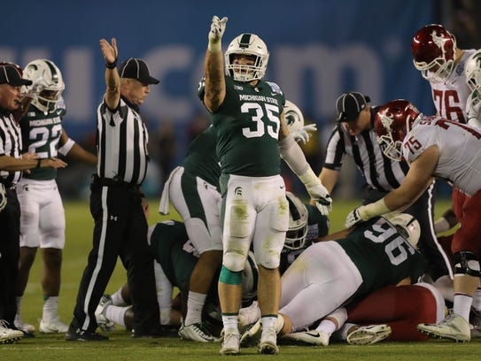 Joe Bachie celebrates a fumble by Washington State
