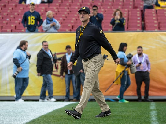 Michigan Wolverines head coach Jim Harbaugh enters