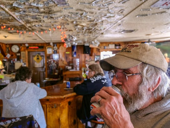 Mike Williams, 62, of Sugar Island enjoys a beer while