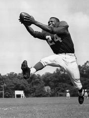 In this July 30, 1953, file photo, veteran halfback Wally Triplett poses in action during his second year with Chicago Cardinals and fourth year in the National Football League.