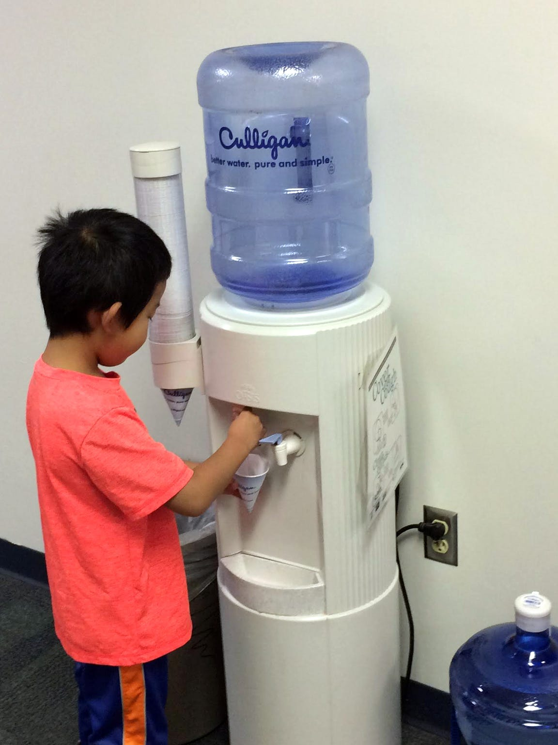 A child gets a drink from a water cooler at Riverside