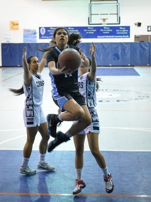 Joy Pangilinan of the St. Paul Warriors splits the Cougars' zone and lays in a 10-foot scoop in an Independent Interscholastic Athletic Association of Guam Girl's Basketball Semifinal Playoff game against the Academy of Our Lady of Guam on Dec. 15.