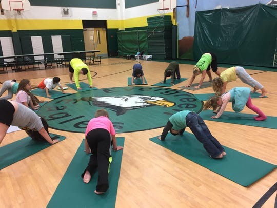 Evergreen Elementary students hold a downward dog pose.