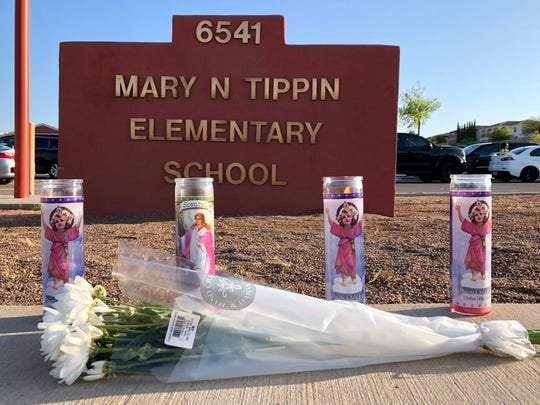 Four candles burn by a bouquet of flowers placed in front of Tippin Elementary School at 6541 Bear Ridge Drive in West El Paso on Tuesday morning after a mother was killed in an accident in the school's parking lot Monday at the end of the first day of school in the El Paso Independent School District.