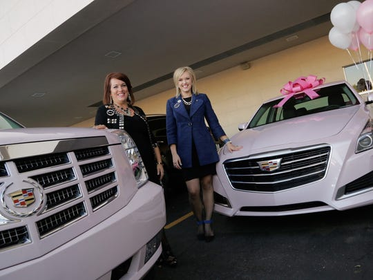 Mary Kay National Sales Director Dawn Otten-Sweeney, left, and her daughter Mary Kay Independent Sales Director Auldon Sweeney-Wydo stand with their pink Cadillacs at the Les Stanford Cadillac dealership in Dearborn on Thursday Oct. 9, 2014, after Auldon received her first pink Cadillac.