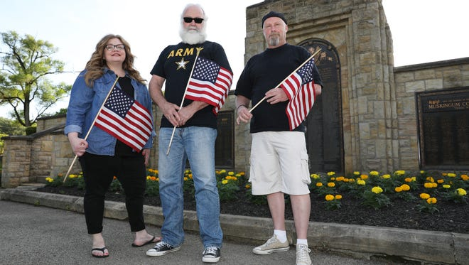Jenifer Ditmar, Don Pagath and Harry Taylor are part of the crew from Zanesville American Legion Post 29 that place flags on veterans' graves at Zanesville Memorial Park.