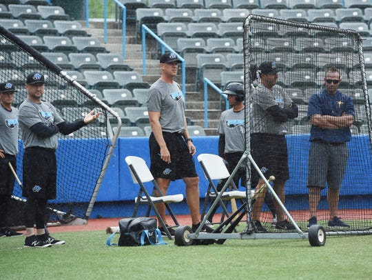 Coaching staff waits behind home plate as it starts