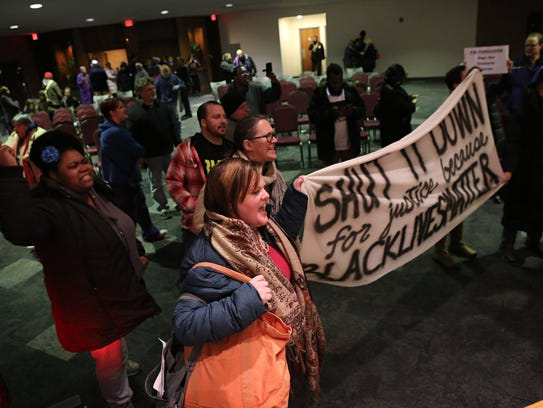 Protesters chant after the Ferguson, Mo., city council