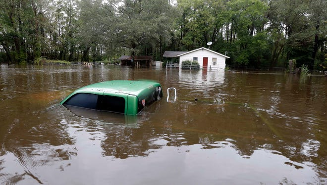 A vehicle and a home are swamped with floodwater from nearby Black Creek in Florence, S.C., on Oct. 5, 2015.