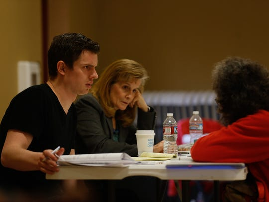 University of Denver third year law student Matthew Kilby, left, and New Mexico attorney Patricia Simpson, middle, work with a client, on Wednesday during the Tribal Wills Project at the Upper Fruitland Chapter House.