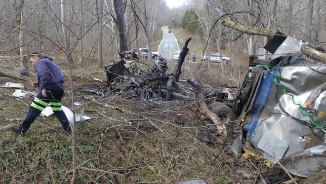 Joe Adamson of STI Towing walks past the wreckage of a tanker truck at the intersection of Dale Williamson Rd. and Big Jimmy Hill Rd. in western Boone County.