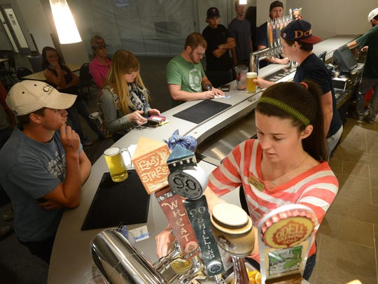 Ella Gilbert pours a beer for a CSU student at the