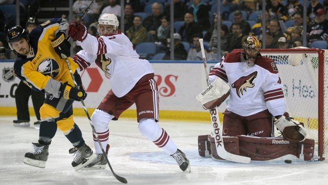 Buffalo Sabres right winger Brian Gionta (12) tangles with Arizona Coyotes defenseman John Moore, middle, as Coyotes goaltender Mike Smith, right, makes a save during the first period of an NHL hockey game Thursday, March 26, 2015, in Buffalo, N.Y.
