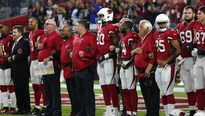 Arizona Cardinals players and coaches link arms during the National Anthem before Monday Night Football against the Cowboys at University of Phoenix Stadium in Glendale, Ariz. September 25, 2017.