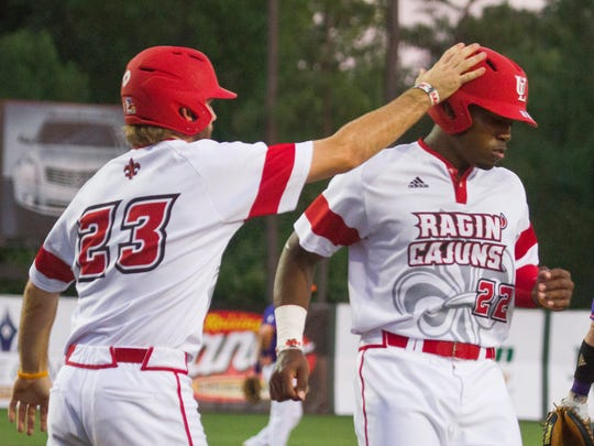 Steven Sensley (22) is congratulated after scoring off a hit by Brenn Conrad in UL's win over against Northwestern State Demons on Tuesday night.