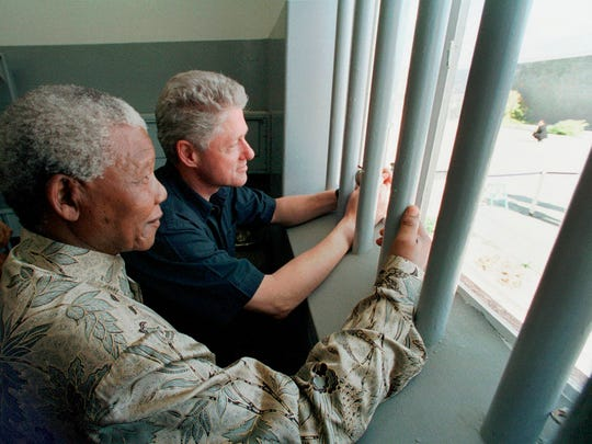 In this March 27, 1998 file photo, Nelson Mandela and former president Bill Clinton look outside from Mandela's Robben Island prison cell,  in Cape Town, South Africa.