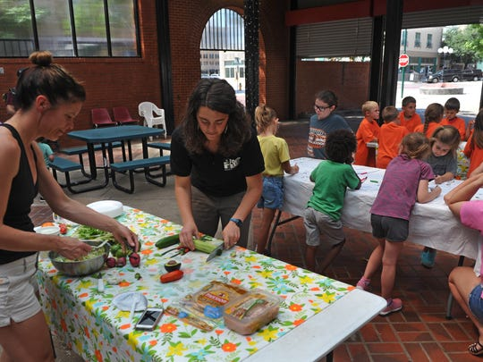 In this file photo, Sherin Clarke, left, Farmers Market manager, and Jessica Bachman, Wichita Falls Area Food Bank, prepare ingredients for veggie wraps during the first Summer Education Program at the Farmers Market. Children learned about preparing and eating healthy snacks.