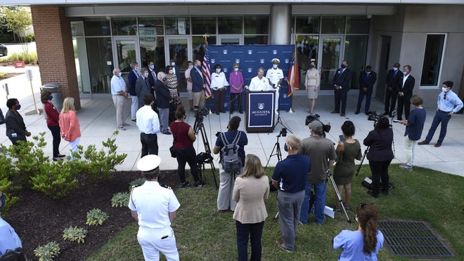 Georgia Gov. Brian Kemp, at lectern, speaks at the Georgia Cancer Center in Augusta on July 2.