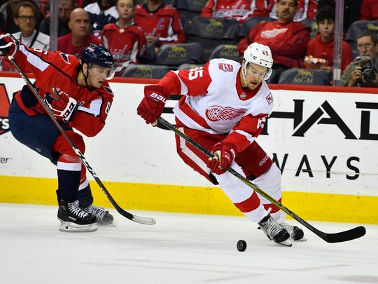 Red Wings defenseman Danny DeKeyser (65) keeps the puck away from Capitals left wing Andre Burakovsky (65) during the first period on Sunday, Feb. 11, 2018, in Washington.