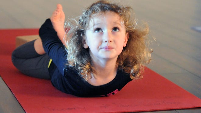 Veronica Suppi, 4, practices boat pose at  Peace Love Yoga in Vineland.