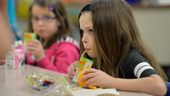 Pleasantview Elementary School kindergartner Makinzey Wheat, right, sips an orange juice box during breakfast in class Friday, Dec. 11 at the school in Sauk Rapids. Free breakfast is served in Sauk Rapids to any student that wants it, one reason that Sauk Rapids-Rice is seeing strong open enrollment figures.