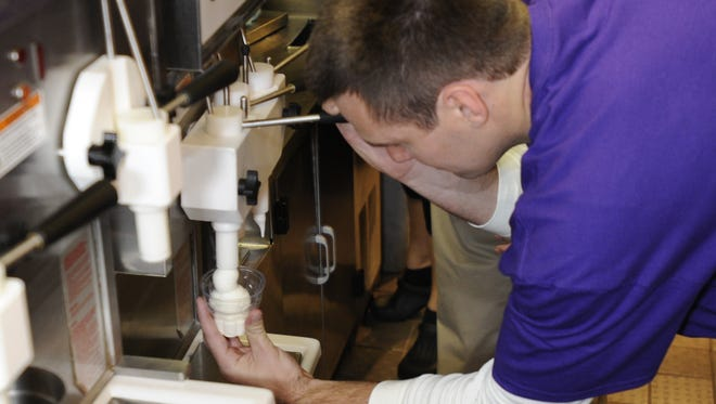 Baltimore Ravens quarterback Joe Flacco learns how to put the curl on a soft-serve ice cream cone at Dairy Queen during a promotional event in 2013.