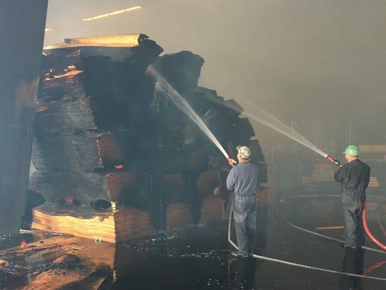 Workers at Freres Lumber Company spray down veneer