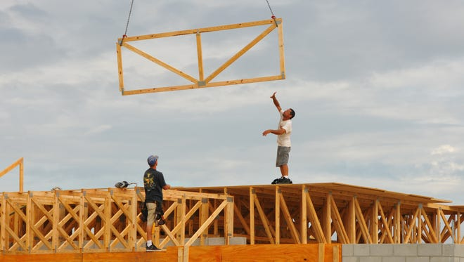 Framers install trusses on a Christopher Burton home under construction in Fairway Lakes at Viera. A proposal before the Brevard County Commission would increase the educational impact fee by $651.10 on a single-family house, effective Jan. 4.