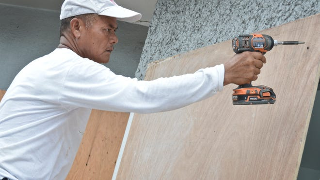 Louis Matawaran of JNG Construction mounts protective plywood over the windows at Auto Spot in East Agana in preparation for Typhoon Chan-hom on July 2.