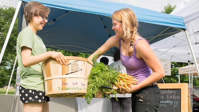 Nashville Food Project intern Catherine Jackson, left, collects donated produce from Sounding Stone Farm owner Caroline McDonald at the Richland Park Farmers' Market on Saturday, June 18, 2016.