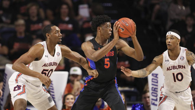 Florida forward Omar Payne (5) spins between Auburn center Austin Wiley (50) and guard Samir Doughty (10) during the first half of an NCAA college basketball game Saturday, Jan. 18, 2020, in Gainesville, Fla.