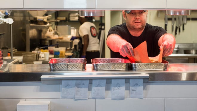Lake's Metro Deli owner and head chef Lake Russell serves up a sandwich in the kitchen at the deli Tuesday.