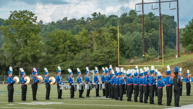 The Patriot marching band stands in formation as Junior ROTC cadets present the flags for the national anthem.