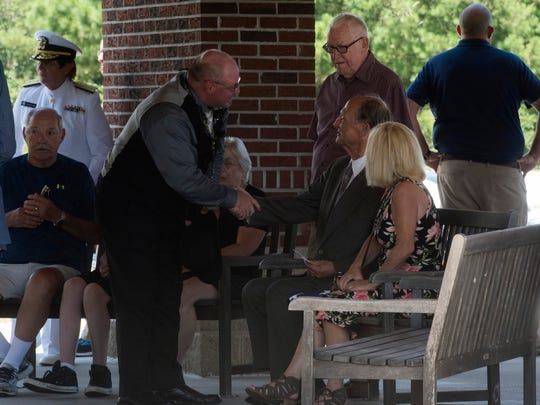 A well-wisher offers his condolences to Robert Schoonover, center, and his daughter, Bobbie Burger following the funeral of his father, John H. Schoonover at Barrancas National Cemetery on Tuesday, June 26, 2018. John H. Schoonover was killed aboard the USS Oklahoma during Pearl Harbor, and through DNA testing his remains were identified and returned to his son, a resident of Panama City, Fla