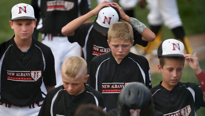 Dejected New Albany, Ind. Little Leaguers leave the field after losing to the Jackie Robinson West Little Leaguers from Chicago at the Central Regional Championship, Aug. 9, 2014.