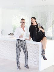 A toast to friendship. At home in Palm Springs, Rob Grace wears Mr Turk pants, a Zara shirt and Gucci loafers. Accessories: Hermès belt,  Cartier and Hermès bracelets, and rings by Tiffany & Co. and Laurie Weitz Collection. His friend, Teresa Parkerson-Rogers, wears an orginal Fedor Rogovets dress, Michael Kors shoes, and jewelry by Laurie Weitz and Renae Madore.
