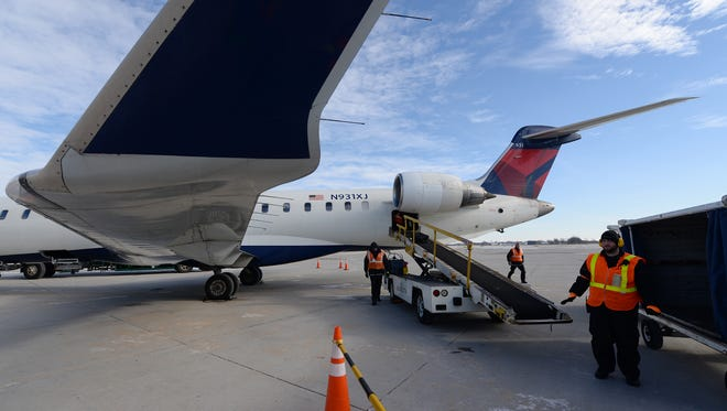 Ground crews at Austin Straubel International Airport scramble to unload baggage and service a Delta flight just arrived from Minneapolis November 20, 2014. Thanksgiving travel is expected to be higher than last year with an estimated 3.55 million passengers traveling by air.