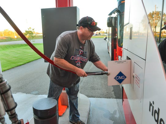 Fueler James Walz fills a MetroBus with compressed