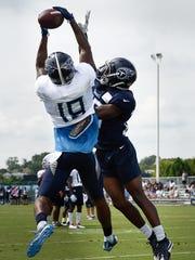 Titans wide receiver Tajae Sharpe (19) pulls down a touchdown pass over cornerback Adoree' Jackson (25) during practice at Saint Thomas Sports Park Wednesday, Aug. 1, 2018, in Nashville, Tenn.