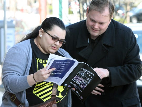 Tatiana Gonzalez of Stroutsburg, Pennsylvania, and Joey Mosca of Jersey City look over the Asbury Park Music in Film Festival guide April 11 before heading to their next event.