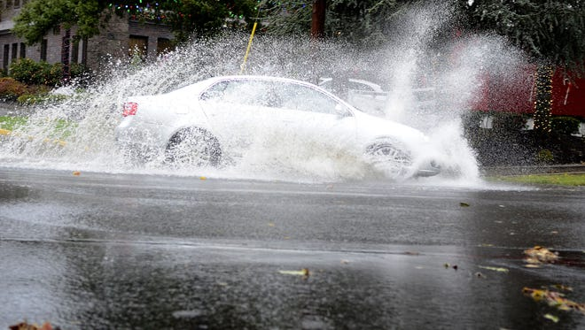 Cars splash through high water on Liberty in South Salem after a heavy rainstorm.