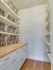 "The spacious pantry combines open shelving with a stylish Schumacher ""Chenonceau"" wallpaper pattern weaving the trend of florals into Carbine's Green Hills home."