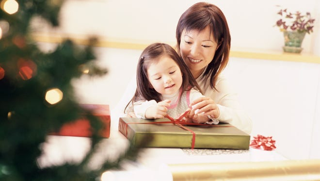 Mother and daughter sit at a table tying a bow on a Christmas present together.