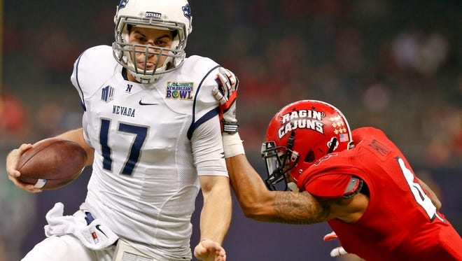 Dec 20, 2014; New Orleans, LA, USA; Nevada Wolf Pack quarterback Cody Fajardo (17) is tackled by Louisiana-Lafayette Ragin Cajuns safety Trevence Patt (4) during the second quarter of the New Orleans Bowl at the Mercedes-Benz Superdome. Mandatory Credit: Derick E. Hingle-USA TODAY Sports