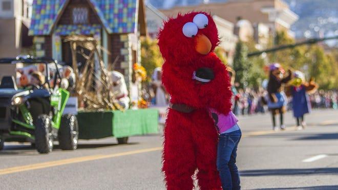 Elmo hugs a child during Cedar City's Storybook Cavalcade Parade Saturday, Nov. 14, 2015.