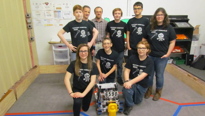 """Ratchet Robotics Team 6590, a group of 8 game teenagers from the Stayton, Aumsville and Turner area, tuned up for the Oregon State Championships in Hillsboro and earned a berth in the FTC West Super Regional competition in Spokane. Pictured with """"Chet"""" the bot, front row, left to right, Marnie Schmidt, Clifford Gamble, Ben Sawyer. Back row, Reese Cureton, Dylan Huffer, adviser Doug Schmidt, Vance Burgess, Javon Baquet, Haley Corpier."""
