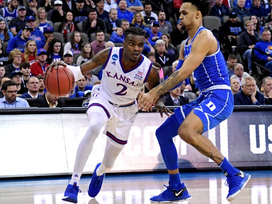 Kansas guard Lagerald Vick drives to the basket against