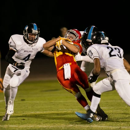 Seton Catholic's George Wolter is tackled by Estrella Foothills defenders on Aug. 29, 2014.
