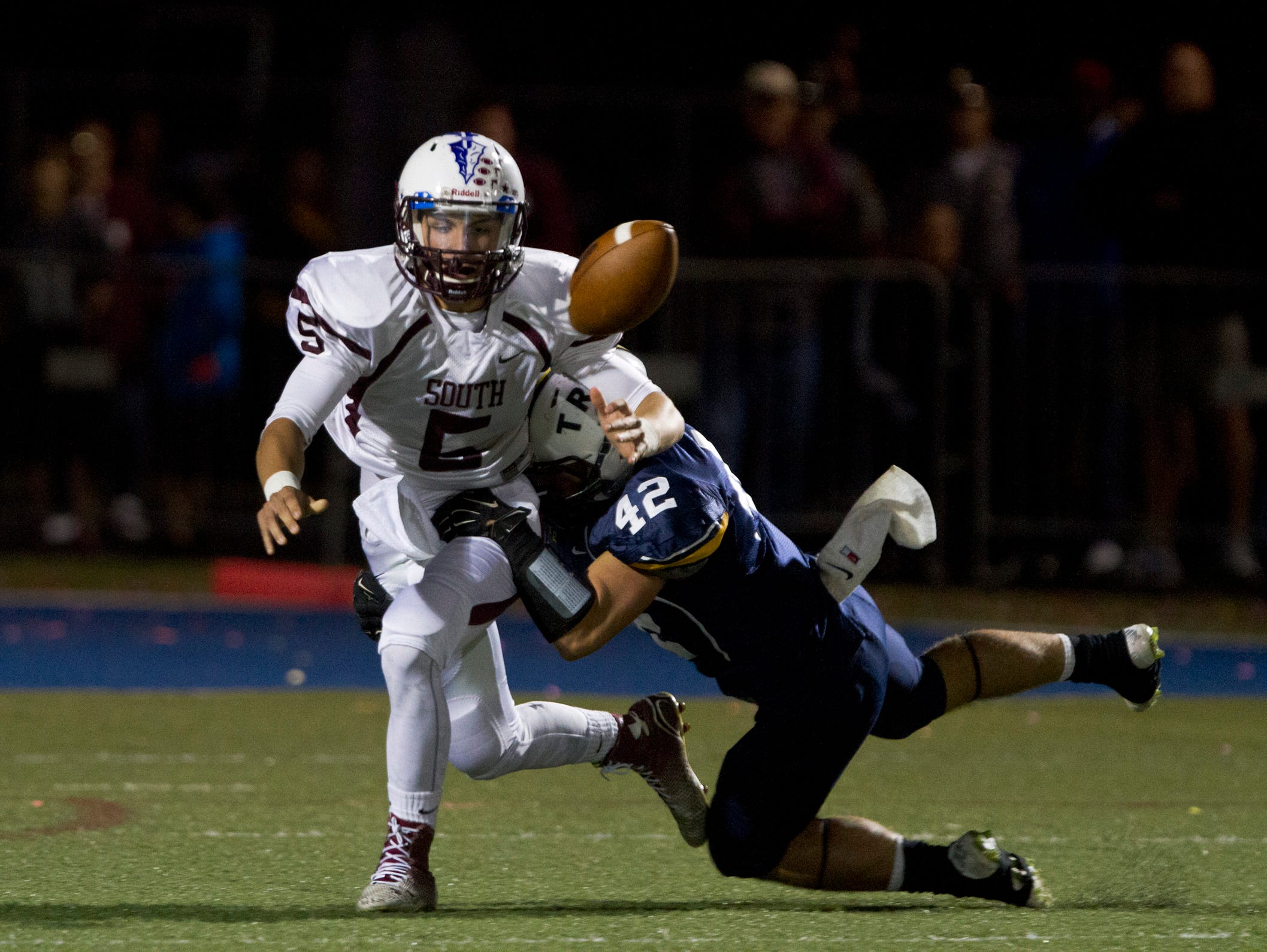Toms River South Quarterback TJ Scuderi loses the ball as he tackled by North's Tommy Donovan and ball was picked up by his North's Pete LaQuaflia and taken join for North's second touchdown. Toms River South vs Toms River North Football in Toms River NJ on September 25, 2015.